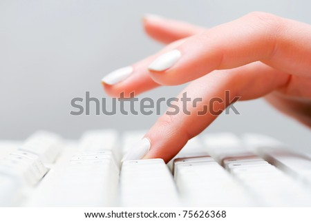 Female hand typing on computer keyboard - stock photo