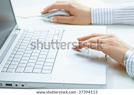 Female hand typing on computer keyboard, using mouse. - stock photo