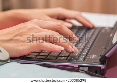 Female hand typing on laptop PC.