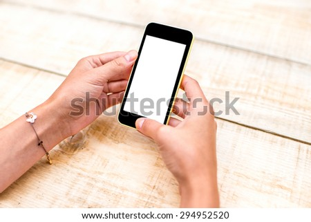 Female hand using a phone with isolated screen on wooden table  - stock photo