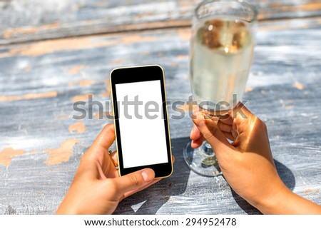 Female hand using a phone with isolated screen on wooden vintage table holding a goblet with champagne - stock photo