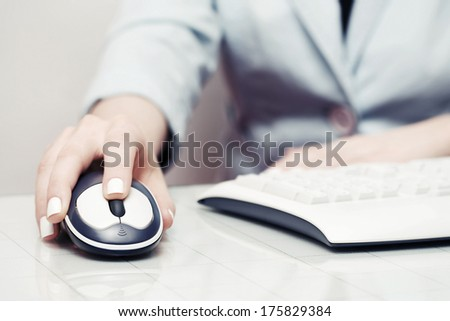 Female hand using computer mouse and keyboard - stock photo