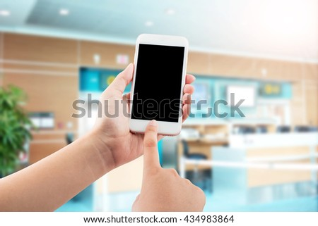 Female hand using mobile smartphone blurred office background - mockup template, clipping path