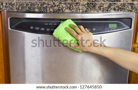 Female hand wiping down front part of stainless steel dishwasher with microfiber towel - stock photo