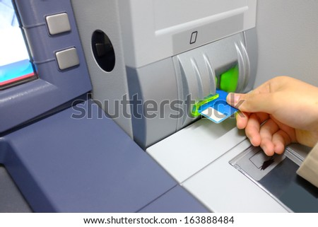 Female hand with a bank card at ATM