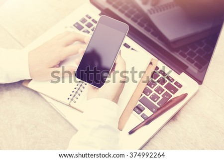Female hand with a blank cell phone and a laptop on the table
