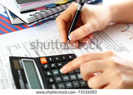 Female  hand  with a calculator and a pen, business  graphics, and  Diagram. - stock photo
