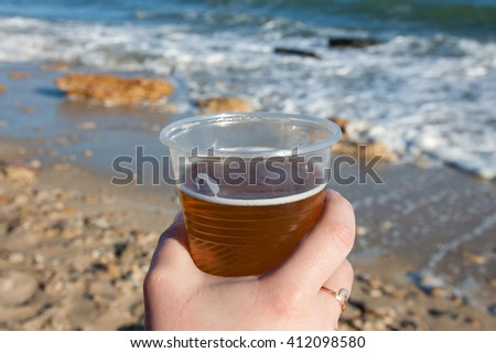 female hand with a glass of beer against the sea - stock photo
