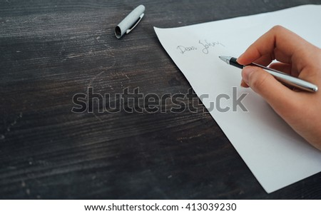 Female hand with a pen writing a letter - stock photo