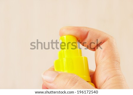 Female hand with a yellow balloon of aerosol close up - stock photo