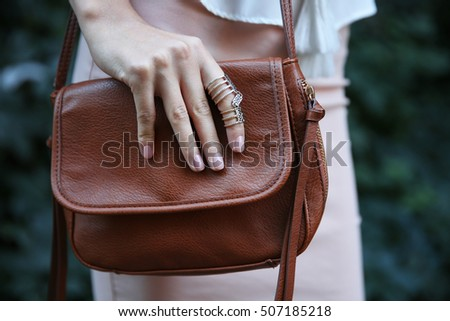 Female hand with bag and stylish ring, closeup