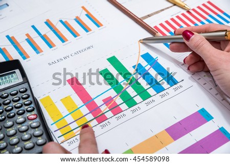 Female hand with business graphics, calculator and pen
