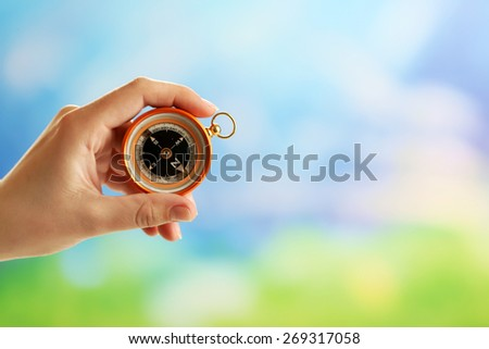 Female hand with compass on bright blurred background - stock photo