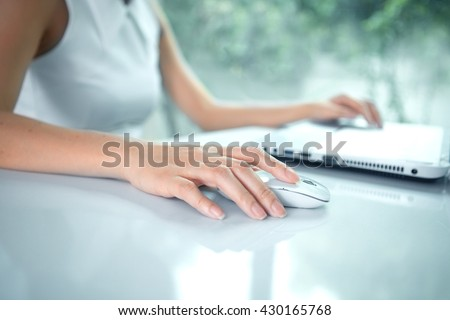 Female hand with computer mouse on table - stock photo