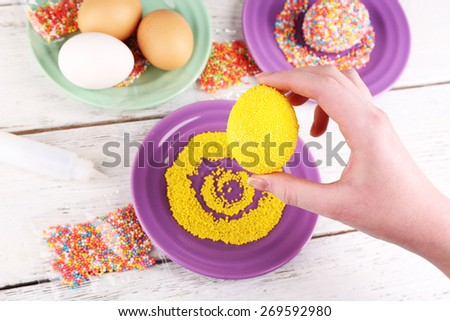 Female hand with decorated Easter egg with colorful beads on wooden table, closeup - stock photo