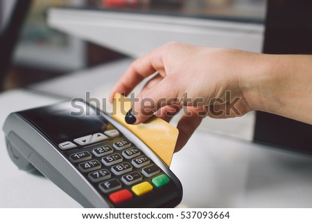 Female hand with golden bank card using the terminal for payment in the shop.