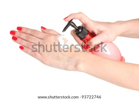Female hand with manicure applying cream on hand isolated on white
