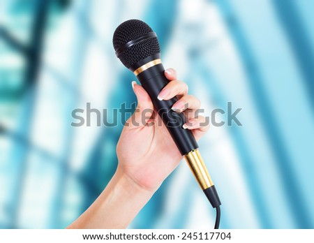 female Hand with microphone - stock photo