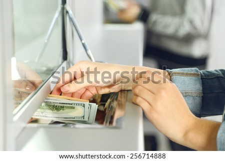 Female hand with money in cash department window. Currency exchange concept - stock photo
