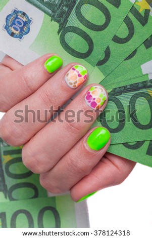 Female hand with multicolored manicure is holding 100 Euro (EUR) banknotes - stock photo