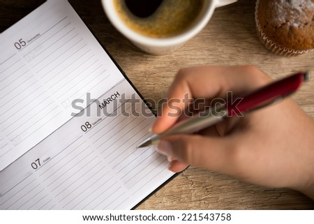Female hand with notebook marks 8 March - stock photo