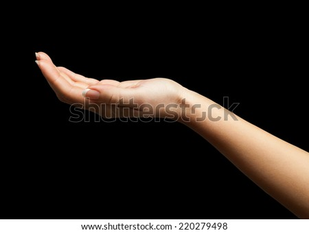 Female hand with open palm over black background - stock photo
