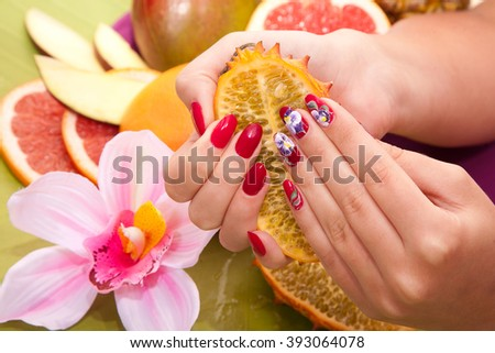 female hand with original red design nails hold a tropical fruit kiwano. Pineapple, grapefruit, mango on the background. Hand care Spa - stock photo