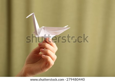 Female hand with paper crane on blurred background - stock photo