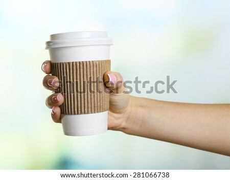 Female hand with paper cup on bright blurred background - stock photo
