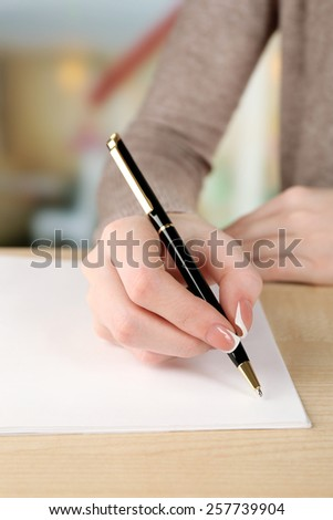 Female hand with pen writing on paper, closeup