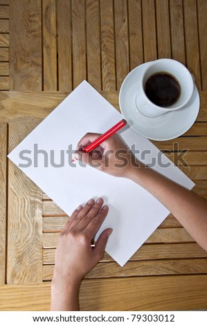 Female hand with pencil writing on a white sheet of paper. Wooden table and a cup of black coffee