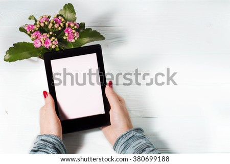 Female hand with red nails, holding e-reader on blue wooden background. Modern book reading. 