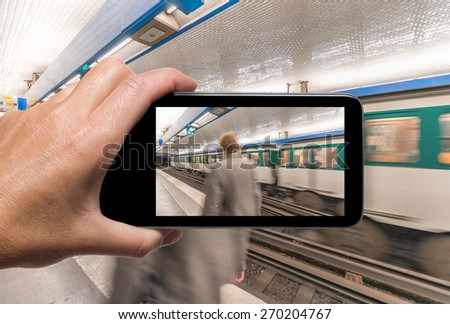 Female hand with smartphone taking a picture of Paris metro station. Tourism concept.