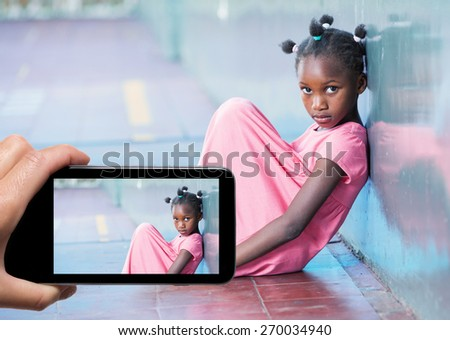 Female hand with smartphone taking a picture of sad girl at primary school. Bullying concept. - stock photo