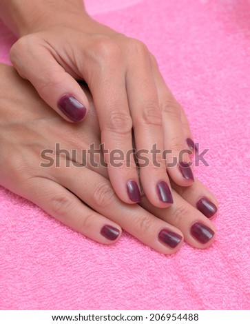 Female hand with stylish colorful nails, on color towel - stock photo