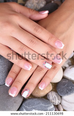 Female hand with stylish colorful nails on sea pebble background