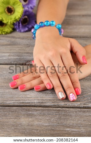 Female hand with stylish colorful nails, on wooden background - stock photo