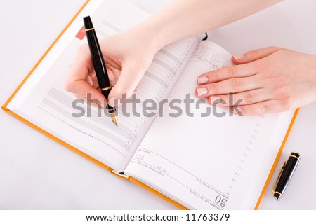 Female hand with the pen/ calendar