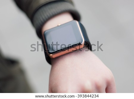 Female hand with trendy smartwatch. Girl is looking for new message or checking time.Modern accessories,stylish touch screen smart watches.Wearable wrist wear.Buy popular gadget.Touch screen watch