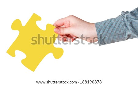 female hand with yellow puzzle piece isolated on white background