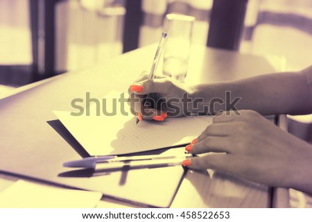Female hand writes, office atmosphere.