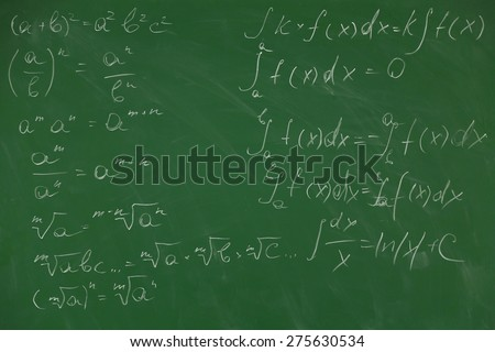 Female hand writing formulas on blackboard with chalk, close up - stock photo