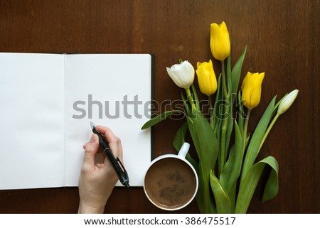 Female hand writing in a book next to a cup of coffee and tulips on a wooden table.