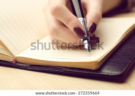 Female hand writing in diary by pen on wooden table background - stock photo