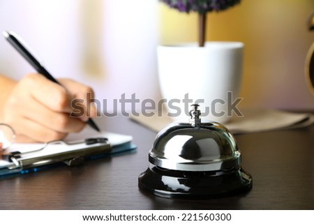 Female hand  writing in Hotel guest book on reception desk, on bright background - stock photo