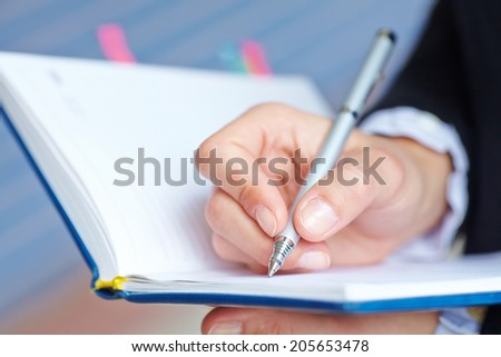 Female hand writing in notebook - stock photo