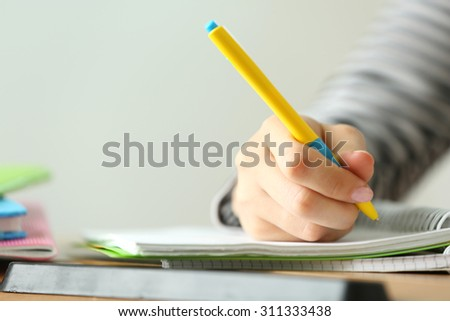 Female hand writing in notebook, close-up - stock photo