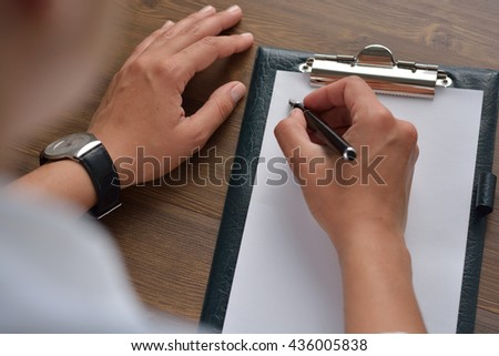 Female hand writing in notebook with pen - stock photo