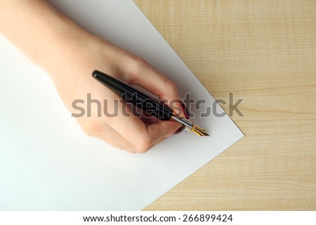 Female hand writing letter on white sheet of paper by fountain pen on wooden table background - stock photo