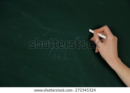 Female hand writing on blackboard with chalk, close up - stock photo